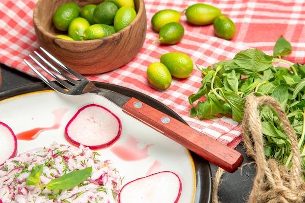 遠くからの側面図格子縞のテーブルクロスに赤みがかったフォークの柑橘系の果物の皿