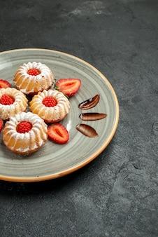 Vista laterale da lontano biscotti appetitosi biscotti appetitosi con fragola e cioccolato su piatto bianco sul lato sinistro del tavolo