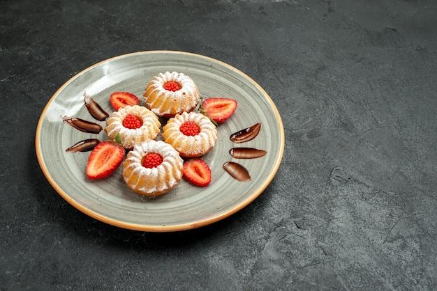 テーブルの左側のプレートにチョコレートとイチゴが入った、遠くからの食欲をそそるクッキークッキーの側面図