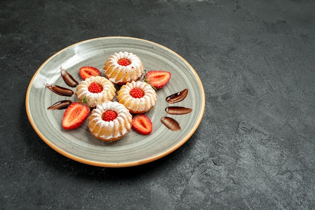 Side view from afar appetizing cookies cookies with chocolate and strawberry in plate on the left side of table