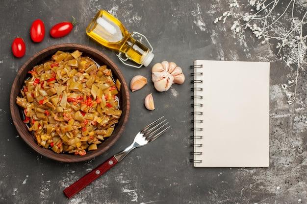 Vista laterale da lontano piatto appetitoso piatto appetitoso accanto alla forchetta bottiglia di olio pomodori aglio e taccuino bianco sul tavolo scuro
