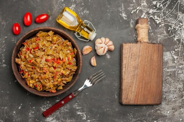 Vista laterale da lontano piatto appetitoso piatto appetitoso accanto alla forchetta bottiglia di olio pomodori aglio e il tagliere di legno sul tavolo scuro