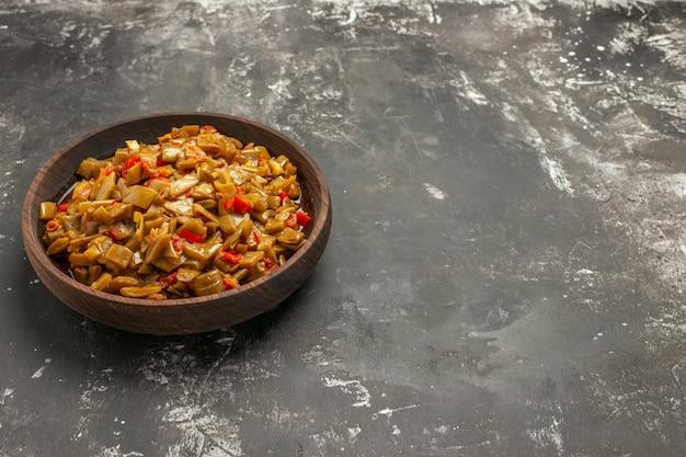 暗いテーブルの左側にあるトマトとサヤインゲンの食欲をそそる料理の遠方からの側面図
