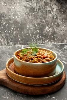 Vista laterale da lontano piatto appetitoso gli appetitosi fagiolini e pomodori sul tagliere sul tavolo nero