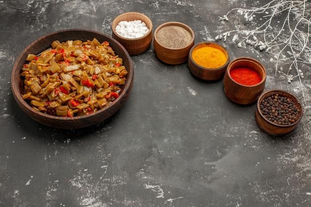 Vista laterale da lontano piatto appetitoso cinque ciotole di spezie colorate accanto al piatto marrone degli appetitosi fagiolini e pomodori