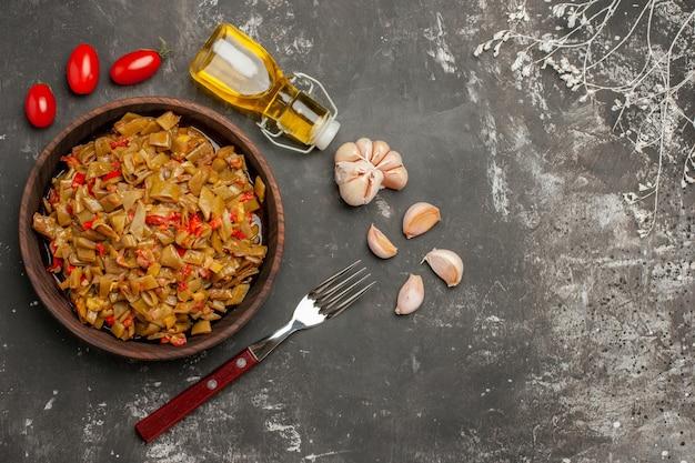 Vista laterale da lontano piatto appetitoso aglio bottiglia di olio pomodori forchetta e un piatto appetitoso accanto ai rami degli alberi sul tavolo scuro