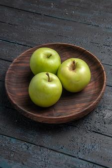 어두운 탁자에 있는 식욕을 돋우는 사과 나무 그릇의 멀리 사과 그릇에서 측면 보기