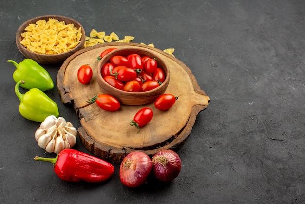 Вид сбоку издалека чаша на доске чаша аппетитных помидоров на разделочной доске рядом с тарелкой пасты болгарского перца и чеснока на столе