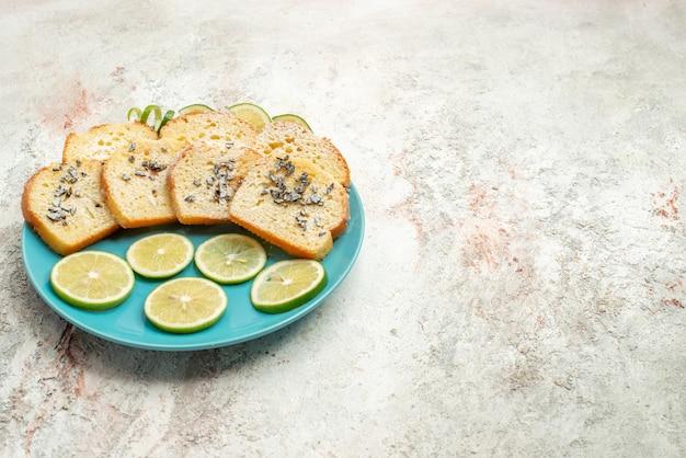 テーブルの上のプレートにハーブレモンとハーブパンと遠くのパンからの側面図