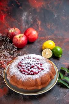 Вид сбоку издалека торт торт с сахарной пудрой три яблока ветки цитрусовых листьев