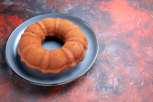 遠くのケーキからの側面図暗いテーブルのプレート上の食欲をそそる丸いケーキ
