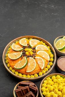 テーブルの上にライムのスライスとライムのチョコレートボウル黄色いキャンディーチョコレートとチョコレートクリームと遠くのケーキとスイーツケーキからの側面図