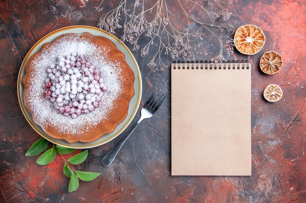 Side view from afar a cake a cake with berries leaves lemon cream notebook fork on the table