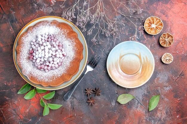 Vista laterale da lontano una torta una torta con foglie di bacche limone forchetta crema piattino anice stellato