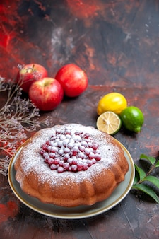 Vista laterale da lontano torta una torta con zucchero a velo tre mele agrumi rami foglie