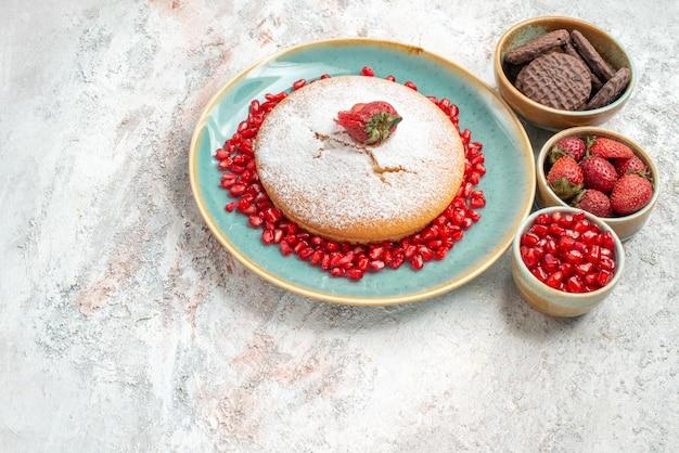 Vista laterale da lontano torta torta con fragole ciotole di biscotti al melograno e frutti di bosco