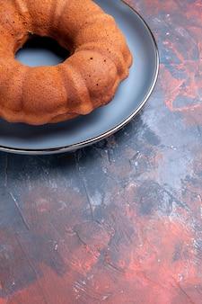 青いプレート上の遠くのケーキ丸いケーキからの側面図