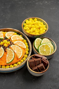 暗い表面にチョコレートライムと黄色いキャンディーのボウルの横にチョコレートと柑橘系の果物とチョコレートケーキと遠くのケーキからの側面図