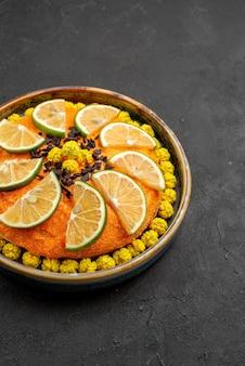 Vista laterale da lontano torta con torta all'arancia con agrumi a fette nella ciotola sul lato sinistro del tavolo scuro