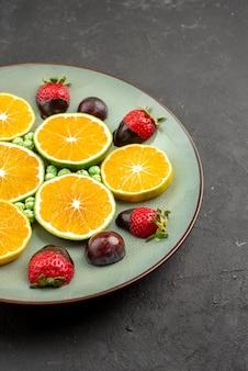 멀리서 초콜릿으로 덮인 딸기 다진 오렌지색 녹색 사탕과 검은 테이블 왼쪽에 있는 식욕을 돋우는 초콜릿 덮인 딸기의 측면