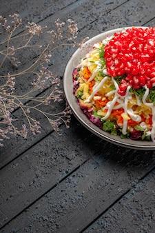 Vista laterale da lontano piatto natalizio piatto natalizio con appetitosi semi di melograno accanto ai rami degli alberi sulla superficie grigia