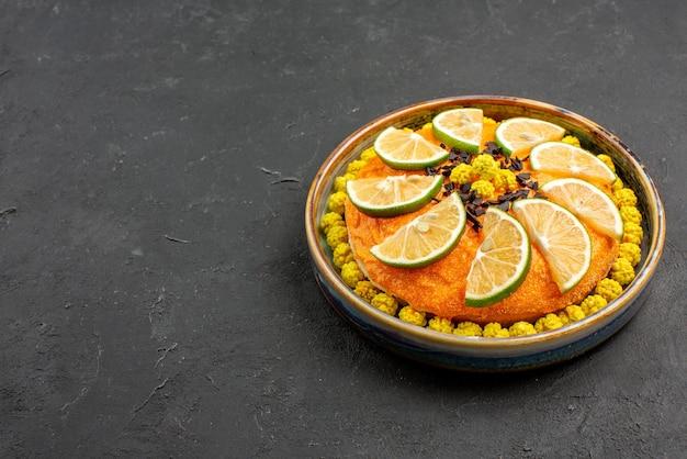 黒いテーブルの右側にチョコレートと柑橘系の果物と遠くの柑橘系の果物とチョコレートケーキからの側面図