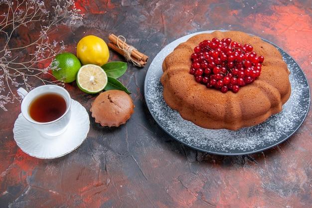 Vista laterale da lontano agrumi una tazza di torta cupcake tè con bacche cannella rami di lime