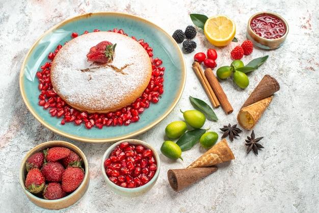 Vista laterale da lontano biscotti e torta una torta marmellata di bacche di melograno limone cannella anice stellato