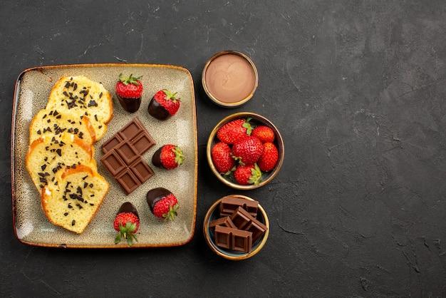 暗いテーブルのボウルにレモンとチョコレートクリームとイチゴが入ったお茶の横にあるチョコレートで覆われたイチゴとケーキの灰色のプレートと遠くのお茶の側面図
