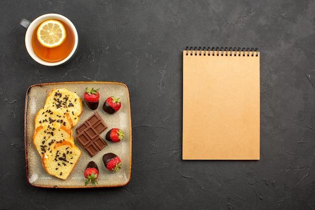 어두운 탁자에 레몬과 크림 공책이 있는 차 한 잔 옆에 초콜릿으로 덮인 딸기가 있는 케이크 회색 케이크 접시가 있는 차 한 잔의 측면