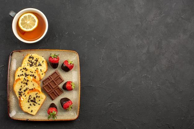 テーブルの左側にあるレモンとお茶のカップの横にチョコレートで覆われたイチゴとケーキの灰色のプレートとケーキの遠方からの側面図