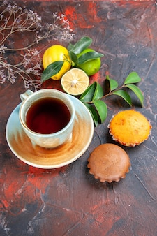 Side view from afar a cup of tea a cup of tea the appetizing citrus fruits with leaves cupcakes