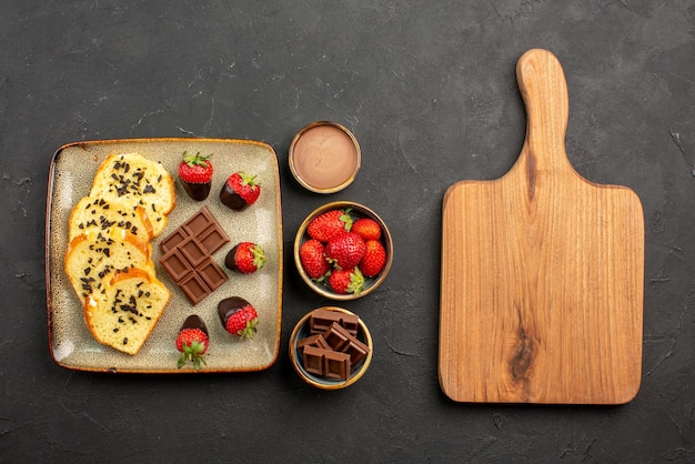 Vista laterale da lontano tazza di tè con torta piatto di torta con fragole ricoperte di cioccolato tazza di tè crema al cioccolato e fragole in ciotole accanto al tagliere