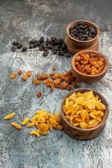 Vista laterale da lontano frutti secchi gli appetitosi frutti secchi colorati nelle ciotole marroni
