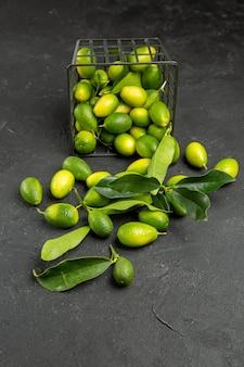 Vista laterale da lontano frutti i frutti appetitosi con foglie sul tavolo