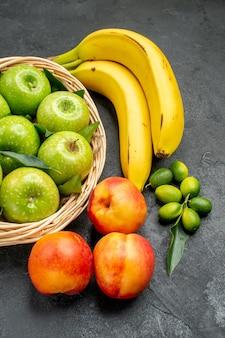 Vista laterale da lontano cesto di frutta di mele verdi lime nettarine e banane sul tavolo