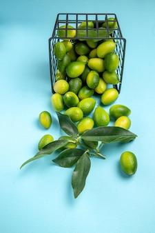 Vista laterale da lontano cesto di frutta di agrumi giallo-verde con foglie sul tavolo blu