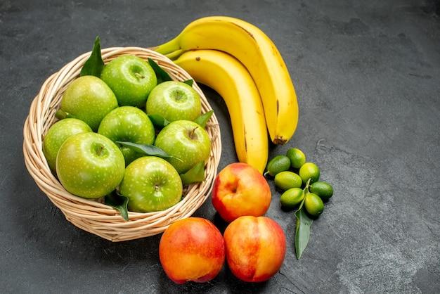 Vista laterale da lontano agrumi banane mele nel cesto nettarine sul tavolo