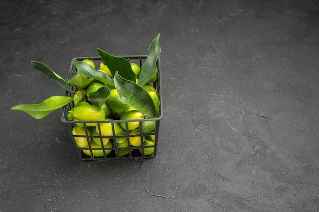 Vista laterale da lontano frutti frutti con foglie nel cesto sul tavolo scuro