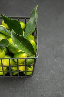 Vista laterale da lontano frutti frutti con foglie nel cesto