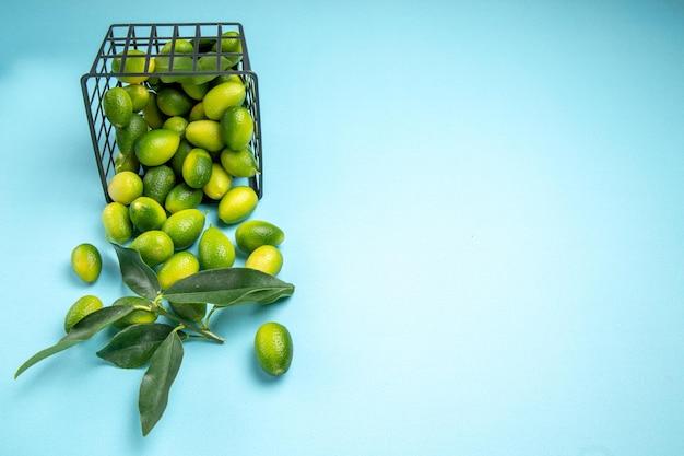 青いテーブルのバスケットに葉を持つ遠くの果物緑黄色の果物からの側面図