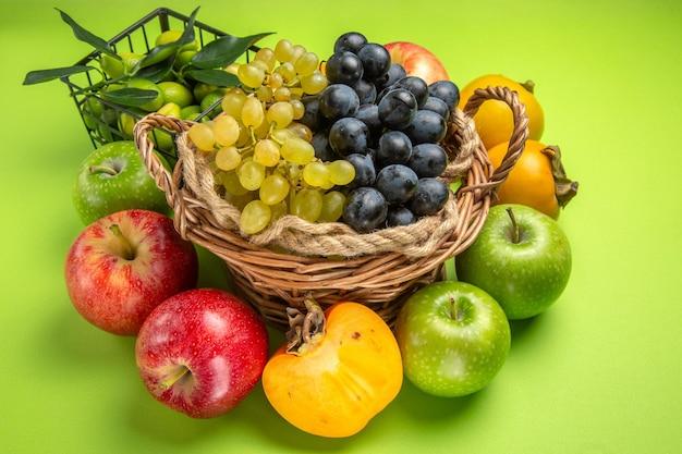 Vista laterale da lontano cesto di legno di frutti di uva mele cachi agrumi