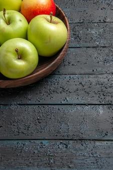 Вид сбоку издалека зелено-желто-красные яблоки зелено-красно-желтые яблоки в тарелке на левой стороне стола