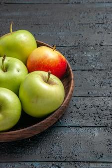 Вид сбоку издалека зелено-желто-красноватых яблок деревянная миска зелено-красно-желтых яблок на левой стороне деревянного стола