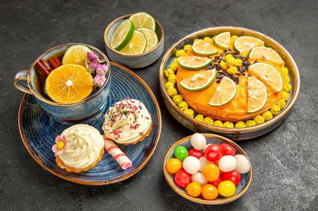 Вид сбоку издалека травяной чай синяя чашка травяного чая с лимоном и корицей рядом с миской ломтиков лайма и сладостей и пирогом с лмесом на темном столе