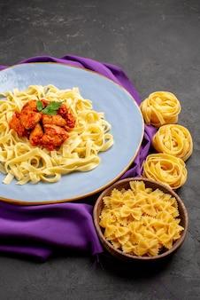 Vista laterale da lontano carne e pasta carne e sugo sulla tovaglia viola e ciotole di pasta sul tavolo scuro