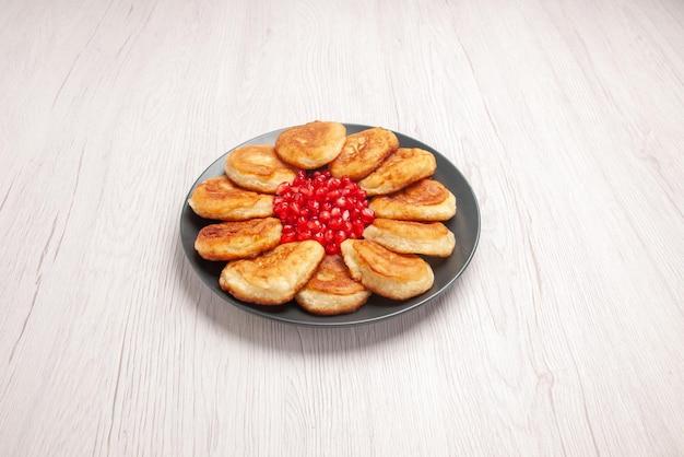 검은 접시에 석류 팬케이크와 석류 씨앗이 있는 멀리 있는 팬케이크의 측면 보기