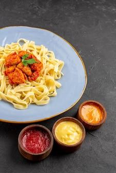 Боковой вид издалека макароны и соусы тарелка пасты с соусом и аппетитным мясом и красочными соусами на столе