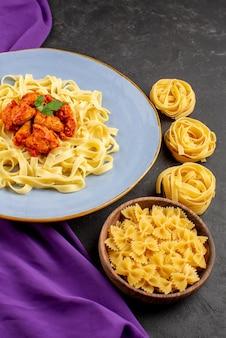 Вид сбоку издалека паста и соусы тарелка пасты с подливкой и мясом рядом с мисками разных видов пасты на фиолетовой скатерти