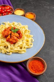 Вид сбоку издалека паста и соусы тарелка пасты с подливкой и мясом рядом с мисками помидоров и соусов на фиолетовой скатерти на темном столе